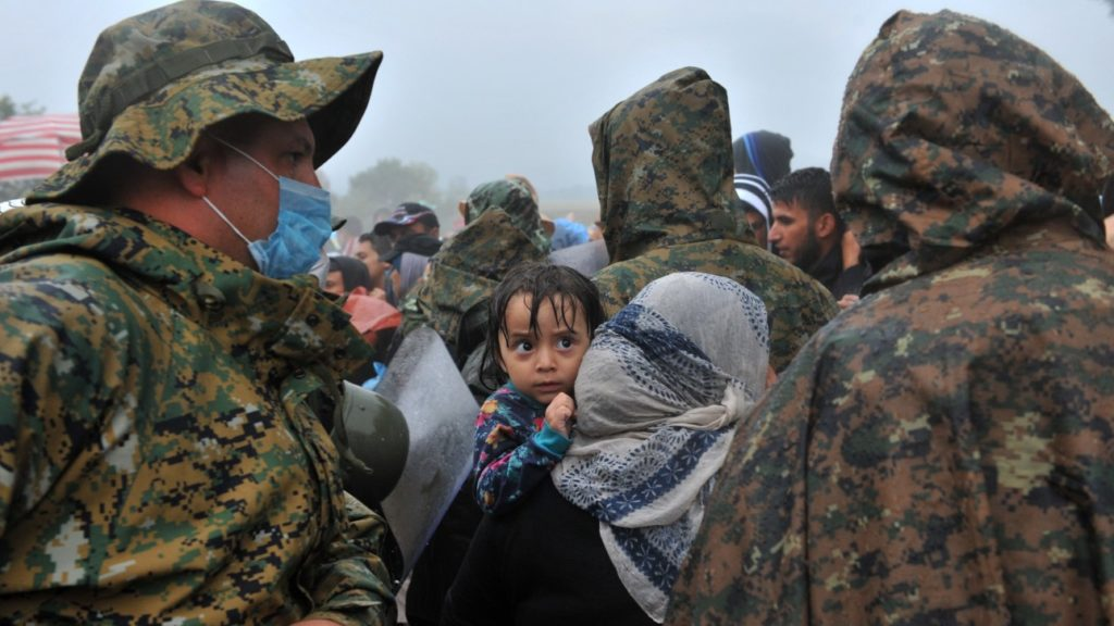 A woman carries her child on his shoulders as migrants and refugees wait under the rain to cross the Greek-Macedonian border near the village of Idomeni, in northern Greece on September 10, 2015. More than 10 thousands refugees and migrants arrived in Piraeus from the overcrowded Greek islands, especially the island of Lesbos , in the last 24 hours.  AFP PHOTO /SAKIS MITROLIDIS        (Photo credit should read SAKIS MITROLIDIS/AFP/Getty Images)